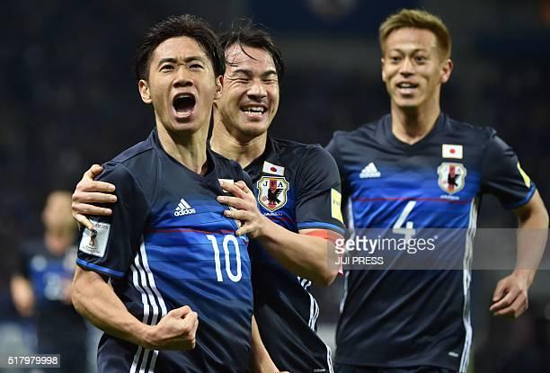 Japan's midfielder Shinji Kagawa celebrates his goal with teammates forward Shinji Okazaki and midfielder Keisuke Honda against Syria during the 2018...