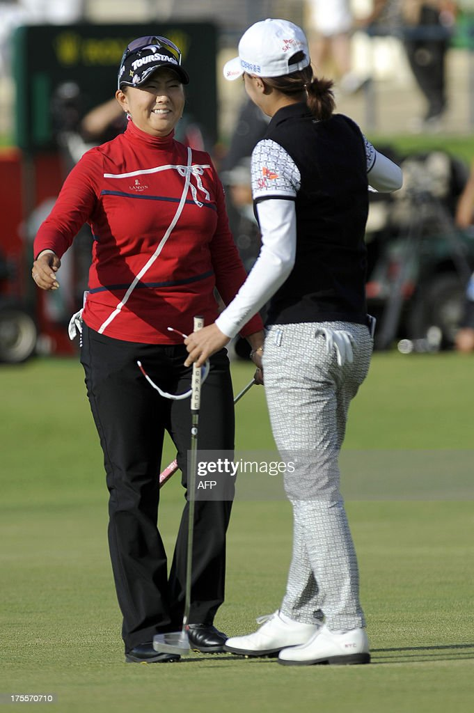 Japan's Miki Saiki (L) embraces Korea's Choi Na Yeon (R) after their final rounds in the Women's British Open Golf Championship at the Old Course in St Andrews, Scotland, on August 4, 2013. US golfer Stacy Lewis won the women's British Open on Sunday by two shots. Lewis, the winner of the 2011 Kraft Nabisco Championship, collected her second major with a final round 72 for an eight-under-par total of 280.