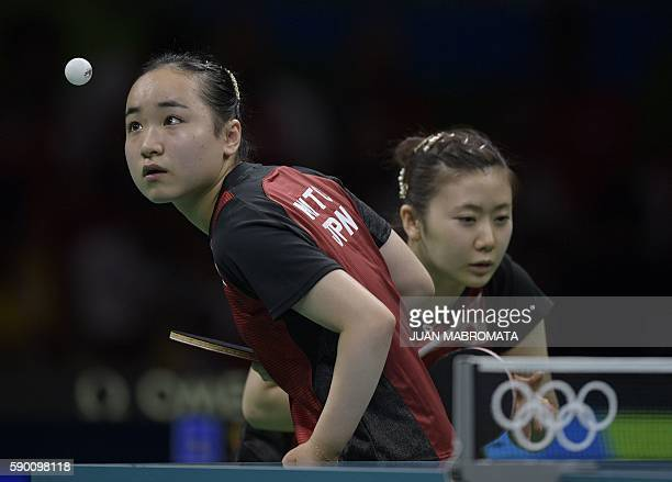 Japan's Mima Ito serves next to Japan's Ai Fukuhara in the women's team bronze medal table tennis match against Singapore's Yu Mengyu and Singapore's...
