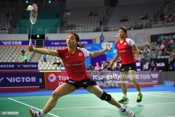 Japan's Misaki Matsutomo plays a shot as her partner Ayaka Takahashi looks on while playing against China's Huang Yaqiong and Yu Xiaohan during their...