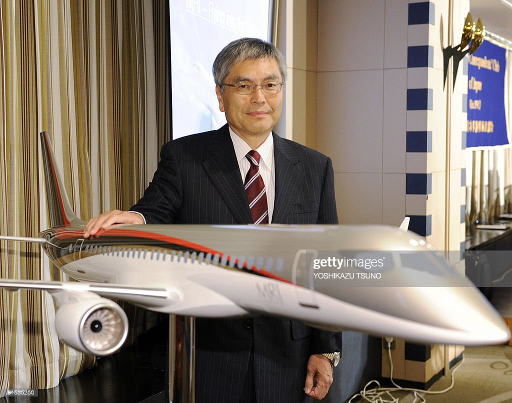 Japan's Mitsubishi Heavy Industries president <a gi-track='captionPersonalityLinkClicked' href=/galleries/search?phrase=Hideaki+Omiya&family=editorial&specificpeople=5398116 ng-click='$event.stopPropagation()'>Hideaki Omiya</a> poses with a scale model of the fuel efficient Mitsubishi Regional jet (MRJ) at a press conference in Tokyo on June 12, 2008. Rising aviation fuel bills could stimulate demand for the MRJ which is expected to take to the skies in 2013. AFP PHOTO / Yoshikazu TSUNO