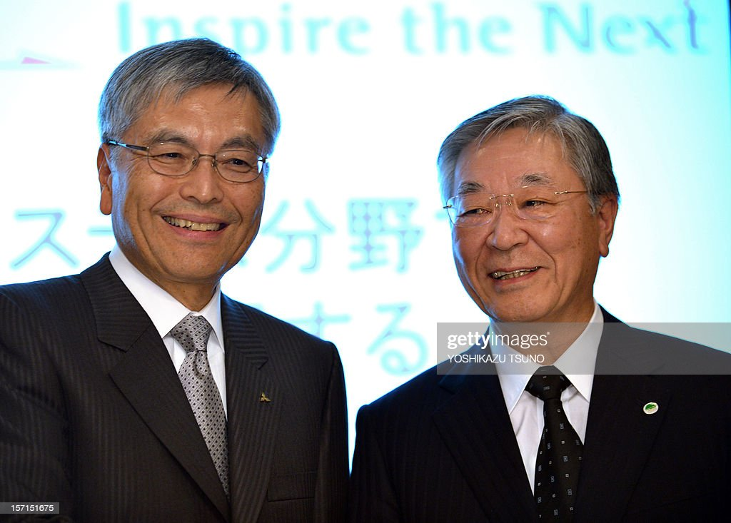 Japan's Mitsubishi Heavy Industries president Hideaki Omiya (L) smiles as he stands with Hitachi president Hiroaki Nakanishi at a press conference in Tokyo on November 29, 2012. Japanese industrial firms Hitachi and Mitsubishi Heavy Industries said on November 29 they would merge their thermal power businesses by 2014 as they take on global giants Siemens and General Electric. AFP PHOTO / Yoshikazu TSUNO