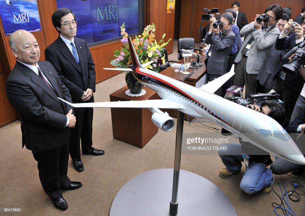 Japan's Mitsubishi Heavy Industries president Kazuo Tsukuda displays a scale model of the company's passenger jetliner 'Mitsubishi Regional Jet ' at...
