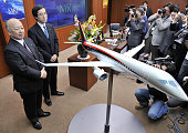 Japan's Mitsubishi Heavy Industries president Kazuo Tsukuda displays a scale model of the company's passenger jetliner 'Mitsubishi Regional Jet ' at...