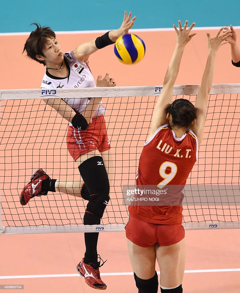 Japan's Miyu Nagaoka (L) spikes the ball past China's Liu Xiaotong (R, #9) during their volleyball match of the FIVB Women's World Grand Prix finals in Tokyo on August 22, 2014. AFP PHOTO / KAZUHIRO NOGI