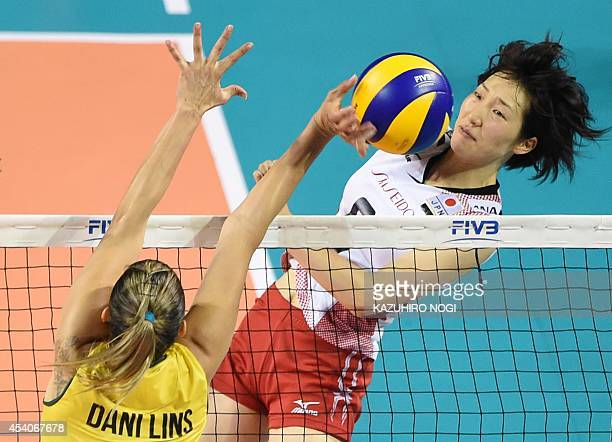 Japan's Mizuho Ishida spikes the ball past Brazil's Danielle Lins during their volleyball match of the FIVB Women's World Grand Prix finals in Tokyo...