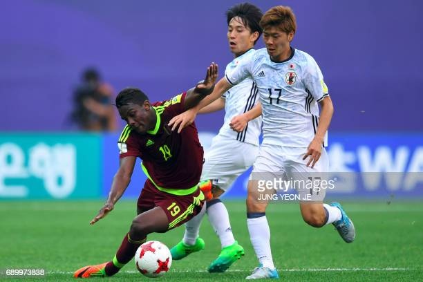 Japan's Mizuki Ichimaru fights for the ball with Venezuela's Sergio Cordova during their U20 World Cup round of 16 football match between Venezuela...