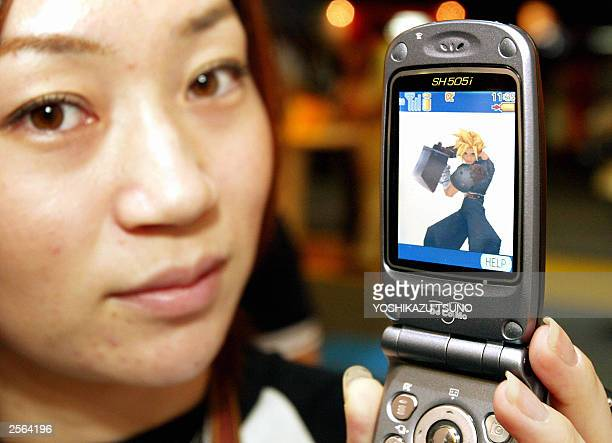 Japan's mobile communication giant NTT DoCoMo employee displays the latest handset SH055i produced by Sharp showing a popular roleplaying game 'Final...