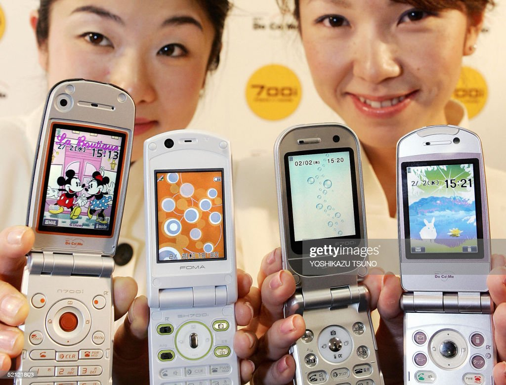 Japan's mobile communication giant NTT DoCoMo employees display the new line up of 3G mobile phone handsets 700i series produced by NEC Sharp Fujitsu...
