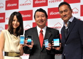Japan's mobile communication giant NTT DoCoMo president Ryuji Yamada and Japanese actors Ken Watanabe and Maki Horikita display new smartphones from...