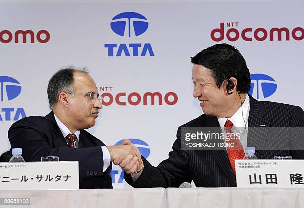 Japan's mobile communication giant NTT docomo president Takamochi Yamada shakes hands with Indian mobile operator Tata Teleservices managing director...