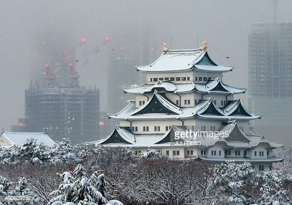 Japan's Nagoya castle is covered with snow in Nagoya in Aichi prefecture central Japan on December 18 2014 as heavy snow hit wide areas of Japan...