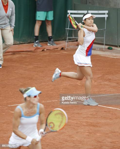 Japan's Nao Hibino hits a backhand alongside Alicja Rosolska of Poland in the women's doubles third round at the French Open in Paris on June 4 2017...