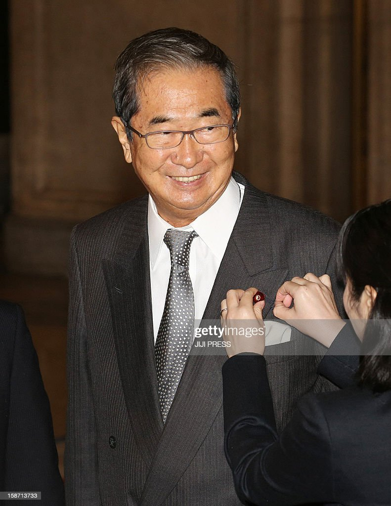 Japan's nationalist politician Shintaro smiles as he receives a Diet member's badge from an official at the National Diet in Tokyo on December 26, 2012. Japan's conservative leader Shinzo Abe is to be named as the country's new prime minister on December 26, after he swept to power on a hawkish platform of getting tough on diplomacy while fixing the economy.