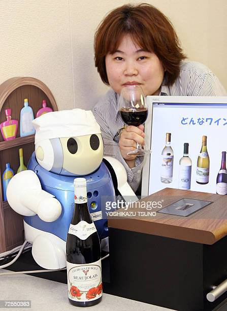Japan's NEC System Technology researcher Kaori Kobayashi demonstrates the company's Sommelier Robot to determine the brand of wine with an infrared...