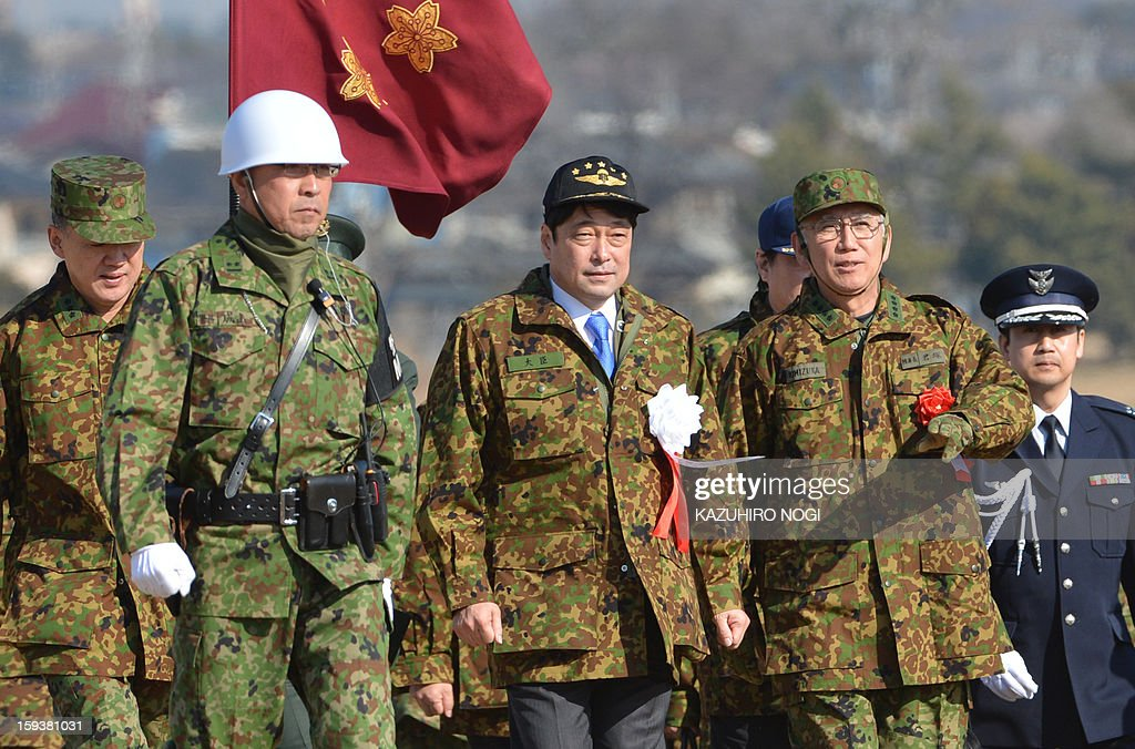 Japan's new Defense Minister Itsunori Onodera (C) arrives at the Japan Self Defense Forces training ground to inspect troops as they parachute in during a new year drill in Narashino, suburban Tokyo on January 13, 2013. A total of 300 personnel, 20 aircraft and 33 vehicles took part in the open exercise at the defense force's Narashino training ground. AFP PHOTO / KAZUHIRO NOGI