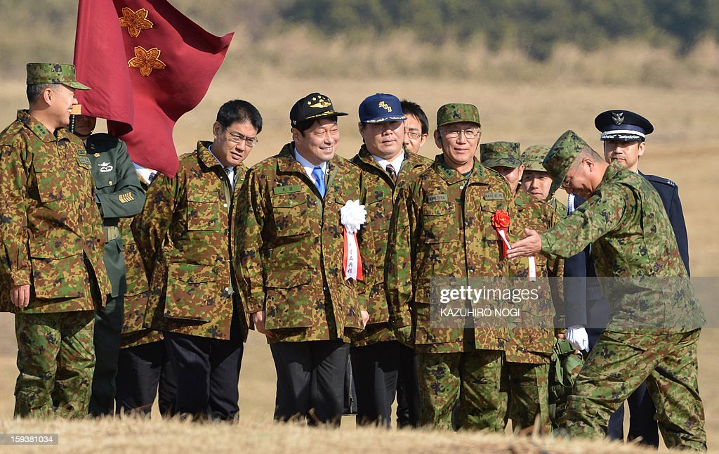 Japan's new Defense Minister Itsunori Onodera (C-black cap) is welcomed as he arrives at the Japan Self Defense Forces training ground to inspect troops as they parachute in during a new year drill in Narashino, suburban Tokyo on January 13, 2013. A total of 300 personnel, 20 aircraft and 33 vehicles took part in the open exercise at the defense force's Narashino training ground.