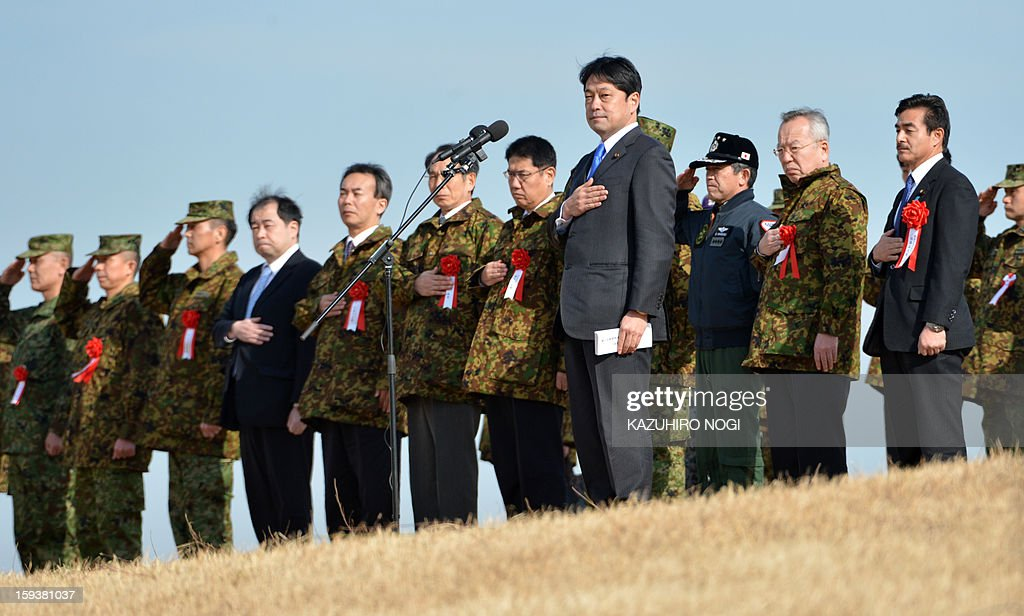 Japan's new Defense Minister Itsunori Onodera (C-front) takes part in a ceremony as he reviews Japan's Self Defense Forces before they parachute in during a new year drill at the training grounds in Narashino, suburban Tokyo on January 13, 2013. A total of 300 personnel, 20 aircraft and 33 vehicles took part in the open exercise at the defense force's Narashino training ground. AFP PHOTO / KAZUHIRO NOGI
