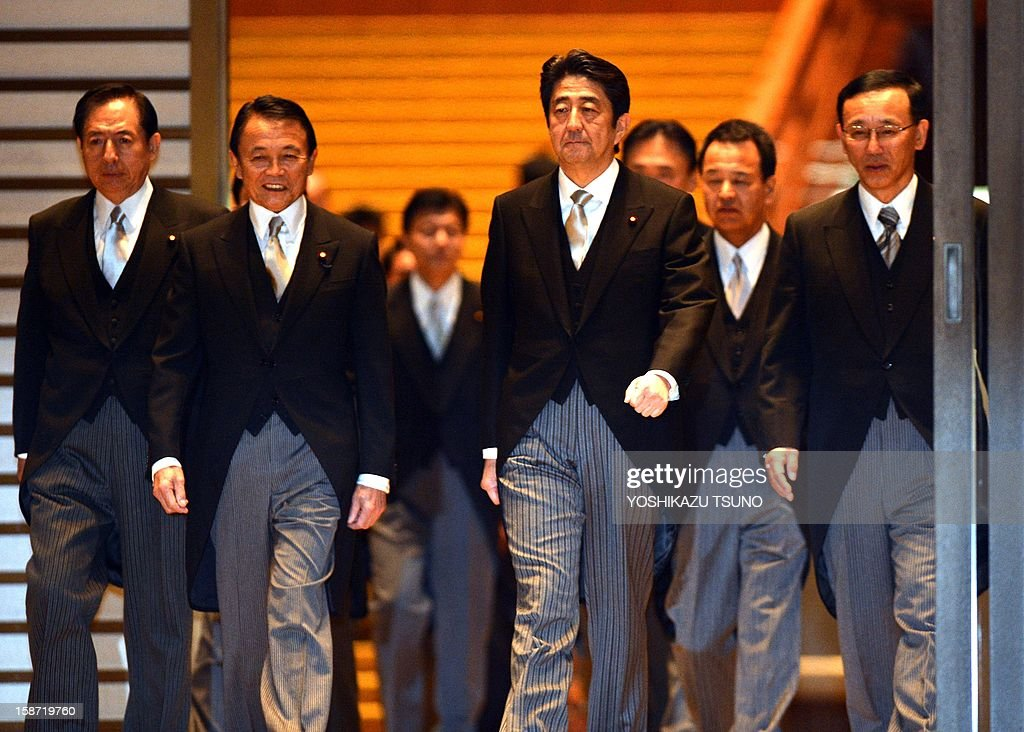 Japan's new Prime Minister Shinzo Abe (C), accompanied by Finance Minister Taro Aso (L) and Justice Minister Sadakazu Tanigaki (R), leads his cabinet members for photo session after they were inaugurated before Emperor Akihito at the Imperial Palace in Tokyo on December 26, 2012. Abe was elected Japan's prime minister by the lower house of parliament after he swept to power on a hawkish platform of getting tough on diplomatic issues while fixing the economy. AFP PHOTO / Yoshikazu TSUNO