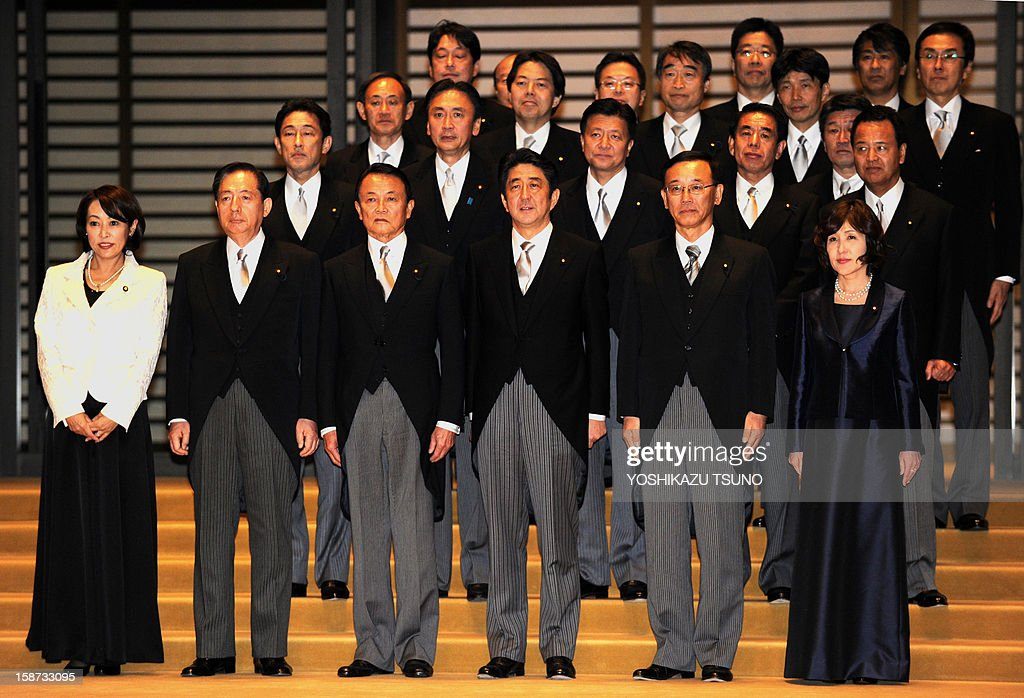 Japan's new Prime Minister Shinzo Abe (C), accompanied by Finance Minister Taro Aso (3rd L) and Justice Minister Sadakazu Tanigaki (2nd R), poses with his cabinet members for a photo session after they were inaugurated before Emperor Akihito at the Imperial Palace in Tokyo on December 26, 2012. Abe was elected Japan's prime minister by the lower house of parliament after he swept to power on a hawkish platform of getting tough on diplomatic issues while fixing the economy. AFP PHOTO / Yoshikazu TSUNO