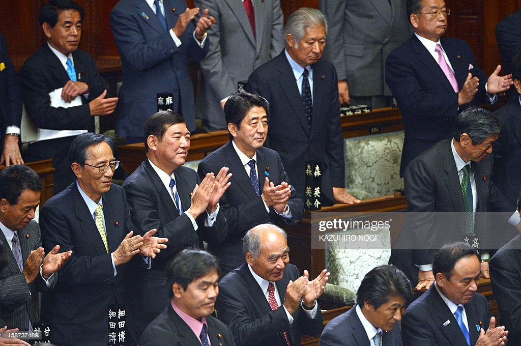 Japan's new Prime Minister Shinzo Abe (C) and fellow members from the ruling Liberal Democratic Party attend a plenary session of the lower house at parliament in Tokyo on December 27, 2012. Abe was elected Japan's prime minister by the lower house of parliament on December 26 after he swept to power on a hawkish platform of getting tough on diplomatic issues while fixing the economy.