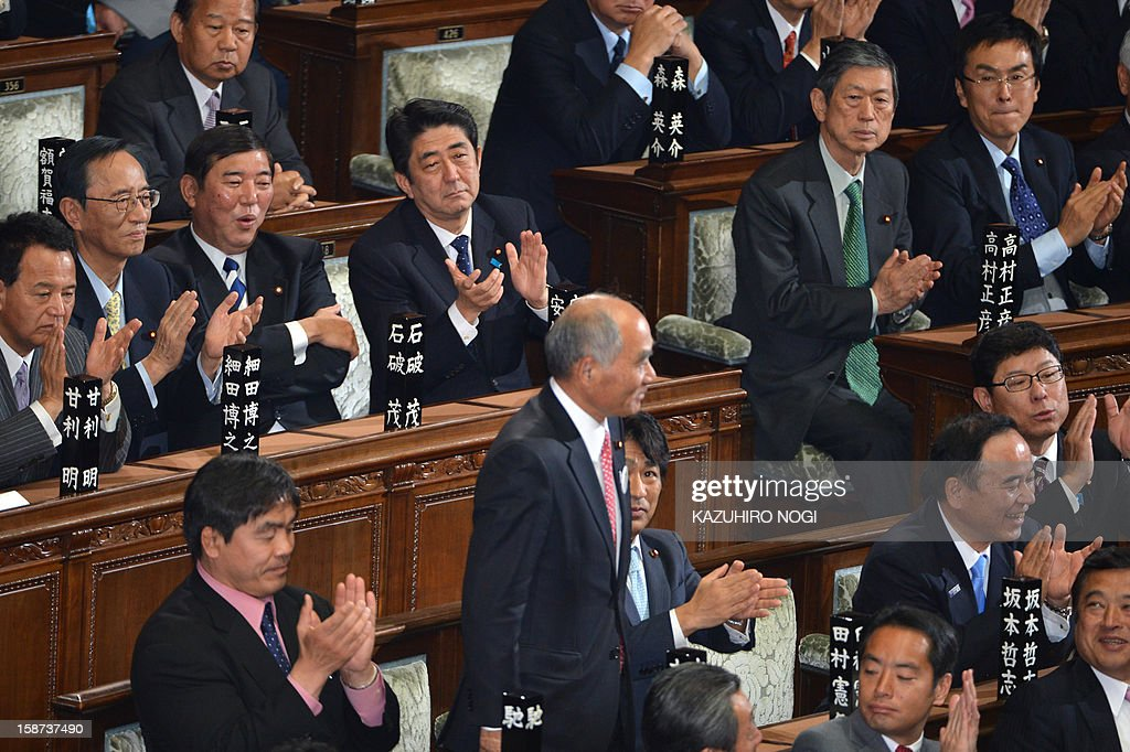 Japan's new Prime Minister Shinzo Abe (C-top) and fellow members from the ruling Liberal Democratic Party attend a plenary session of the lower house at parliament in Tokyo on December 27, 2012. Abe was elected Japan's prime minister by the lower house of parliament on December 26 after he swept to power on a hawkish platform of getting tough on diplomatic issues while fixing the economy. AFP PHOTO / KAZUHIRO NOGI
