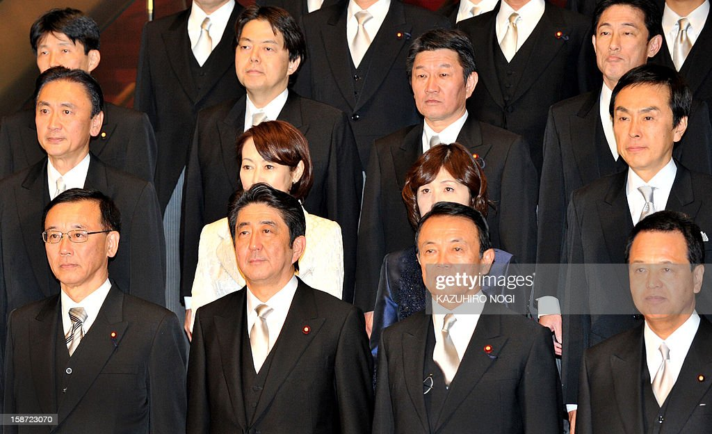 Japan's new Prime Minister Shinzo Abe (front, 2nd L) and his cabinet members step down for a photo session after their first cabinet meeting at the prime minister's official residence in Tokyo on December 26, 2012. Abe was elected Japan's prime minister by the lower house of parliament after he swept to power on a hawkish platform of getting tough on diplomatic issues while fixing the economy.