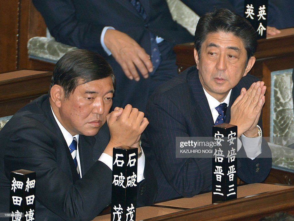 Japan's new Prime Minister Shinzo Abe (R) and Shigeru Ishiba (L), secretary general of the ruling Liberal Democratic Party, attend a plenary session of the lower house at parliament in Tokyo on December 27, 2012. Abe was elected Japan's prime minister by the lower house of parliament on December 26 after he swept to power on a hawkish platform of getting tough on diplomatic issues while fixing the economy. AFP PHOTO / KAZUHIRO NOGI