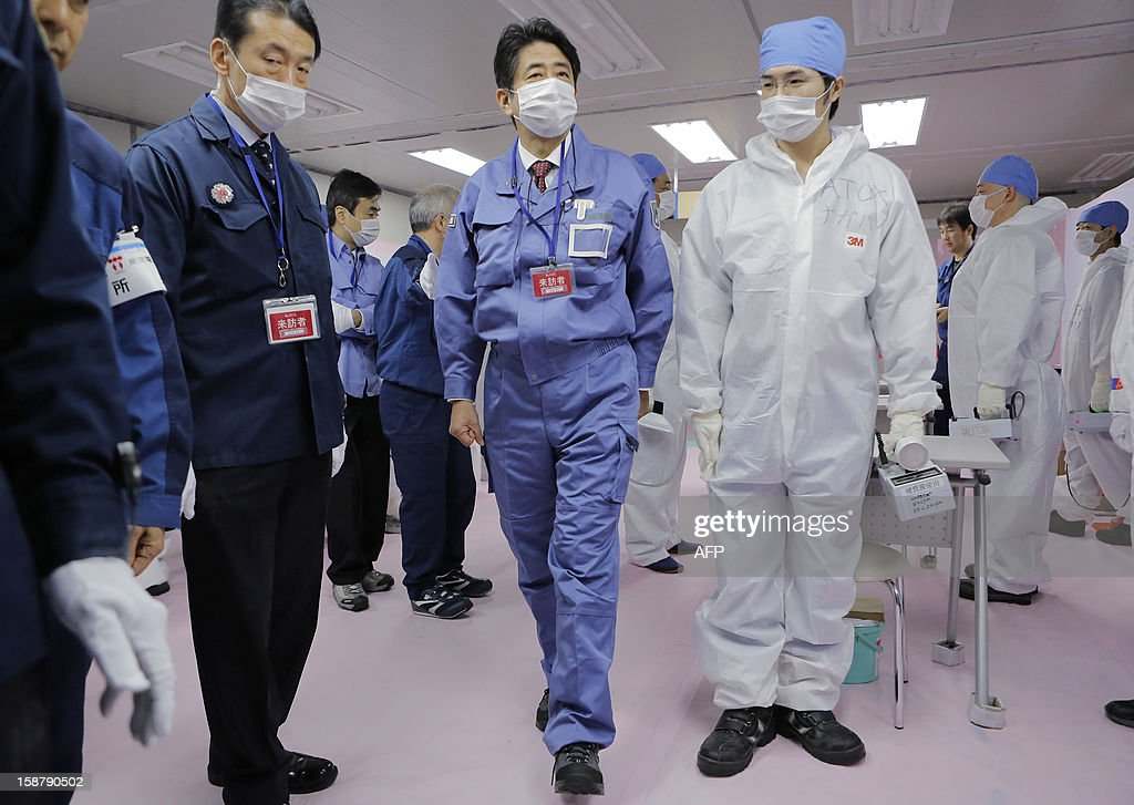 Japan's new Prime Minister Shinzo Abe (C) inspects the Tokyo Electric Power Company's (TEPCO) emergency operation center inside the crippled Fukushima Daiichi nuclear power plant in Ota on December 29, 2012. The clean-up at Fukushima after its tsunami-sparked nuclear meltdowns is an 'unprecedented challenge' Abe told workers during a tour of the plant. AFP PHOTO / Itsuo Inouye / POOL