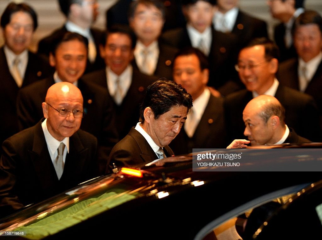 Japan's new Prime Minister Shinzo Abe (C) leaves a photo session with his cabinet members after they were inaugurated before Emperor Akihito at the Imperial Palace in Tokyo on December 26, 2012. Abe was elected Japan's prime minister by the lower house of parliament after he swept to power on a hawkish platform of getting tough on diplomatic issues while fixing the economy. AFP PHOTO / Yoshikazu TSUNO