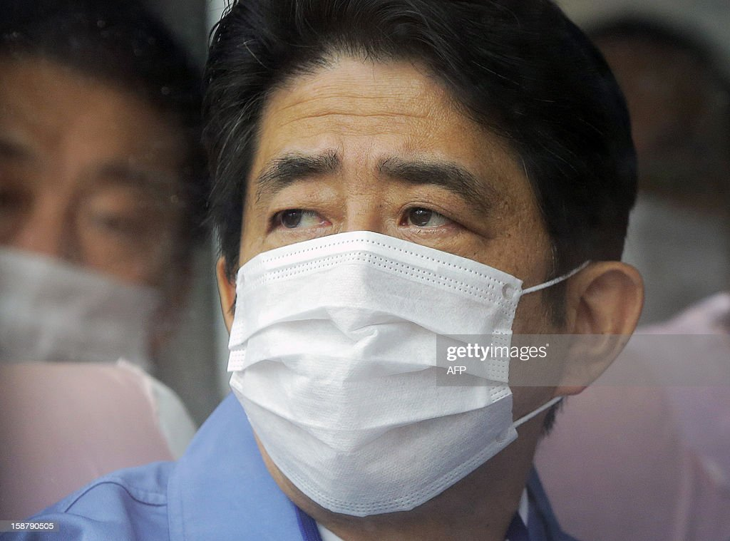 Japan's new Prime Minister Shinzo Abe looks on inside the Tokyo Electric Power Company's (TEPCO) emergency operation center inside the crippled Fukushima Daiichi nuclear power plant in Ota on December 29, 2012. The clean-up at Fukushima after its tsunami-sparked nuclear meltdowns is an 'unprecedented challenge' Abe told workers during a tour of the plant. AFP PHOTO / Itsuo Inouye / POOL