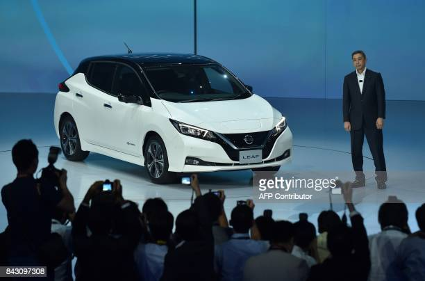 Japan's Nissan Motor President and Chief Executive Officer Hiroto Saikawa stands next to the company's new Nissan LEAF during the world premiere in...