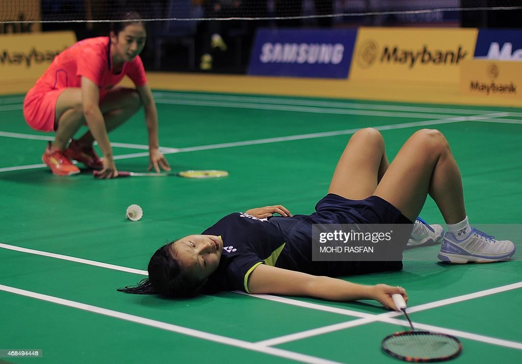 Japan's Nozomi Okuhara (R) reacts after losing a shot as <a gi-track='captionPersonalityLinkClicked' href=/galleries/search?phrase=Wang+Shixian&family=editorial&specificpeople=5777044 ng-click='$event.stopPropagation()'>Wang Shixian</a> of China looks on during their women's quarter-final singles match at the 2015 Malaysia Open badminton championship in Kuala Lumpur on April 3, 2015. AFP PHOTO / MOHD RASFAN