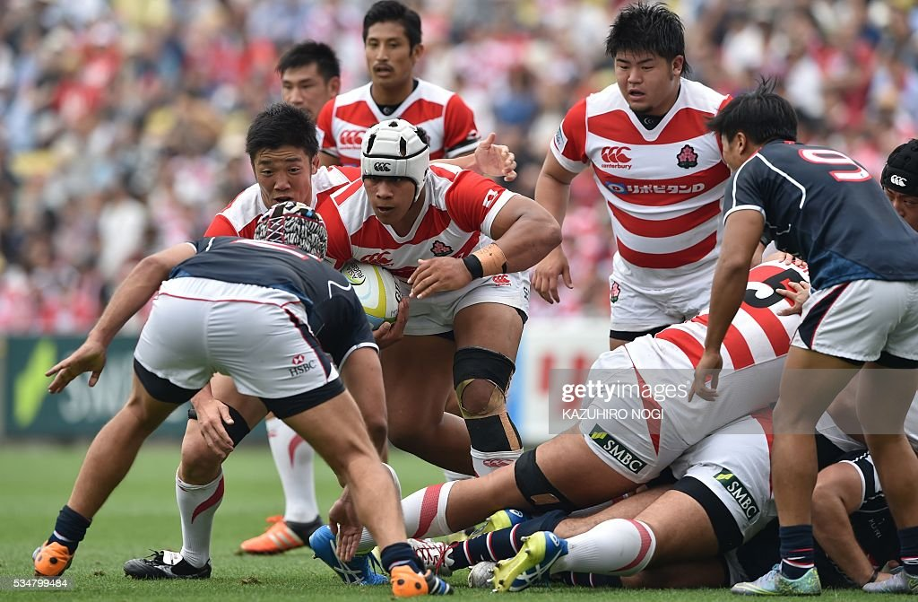 Japan's number eight Tevita Tatafu (2nd L) carries the ball in front of Hong Kong's hooker Lachlan Chubb (L) during their Asia Rugby Championship match at the Prince Chichibu Memorial Rugby Ground in Tokyo on May 28, 2016. / AFP / KAZUHIRO