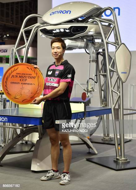 Japan's Olympic medallist Jun Mizutani poses with FORPHEUS a fourthgeneration tabletennis robot developed by automation parts maker Omron during a...