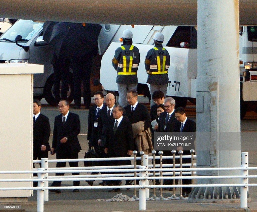 Japan's plant building company JGC president Koichi Kawana (4th L) returns from Algeria while officers use black umbrellas (back) to shield survivors of Algerian hostage crisis after disembarking from from a Japanese government plane, which carried seven survivors and nine dead bodies at the Haneda airport in Tokyo on January 25, 2013. A plane carrying seven survivors of the Algerian hostage crisis, along with nine of the country's ten dead, arrived back in a shell-shocked Japan on January 25. AFP PHOTO / Yoshikazu TSUNO