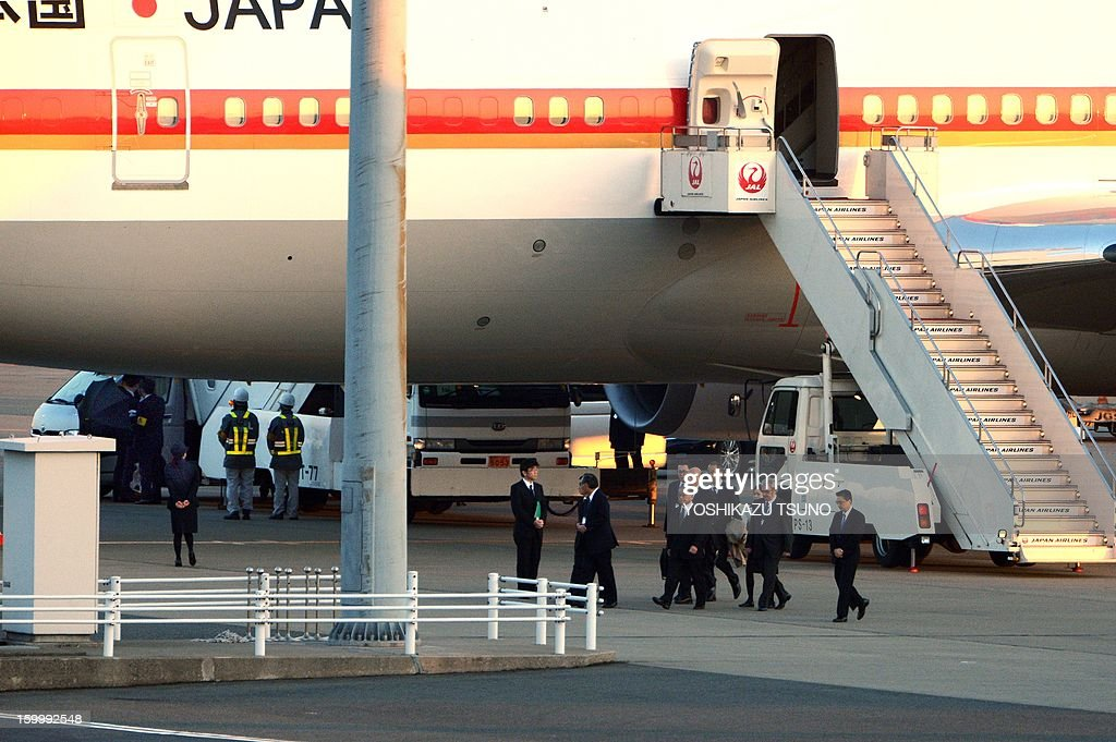 Japan's plant building company JGC president Koichi Kawana (5th R) returns from Algeria while officers use black umbrellas (back L) to shield survivors of the Algerian hostage crisis after disembarking from a Japanese government plane, which carried seven survivors and nine of the country's ten dead at the Haneda airport in Tokyo on January 25, 2013. A plane carrying seven survivors of the Algerian hostage crisis, along with nine of the country's ten dead, arrived back in a shell-shocked Japan on January 25. AFP PHOTO / Yoshikazu TSUNO
