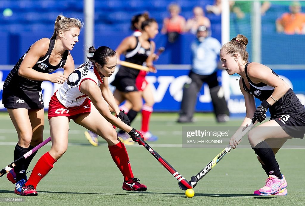 Japan's player Yoshino Kasahara (C) vies for the ball with New Zealand's players Jordan Grant (L) and Samantha Charlton (R) during the Field Hockey World Cup Women's tournament match Japan vs New Zealand on June 7, 2014, in The Hague.