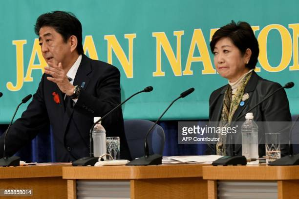 Japan's Prime Minister and President of ruling Liberal Democratic Party Shinzo Abe gestures as he answers questions beside Tokyo Governor and head of...