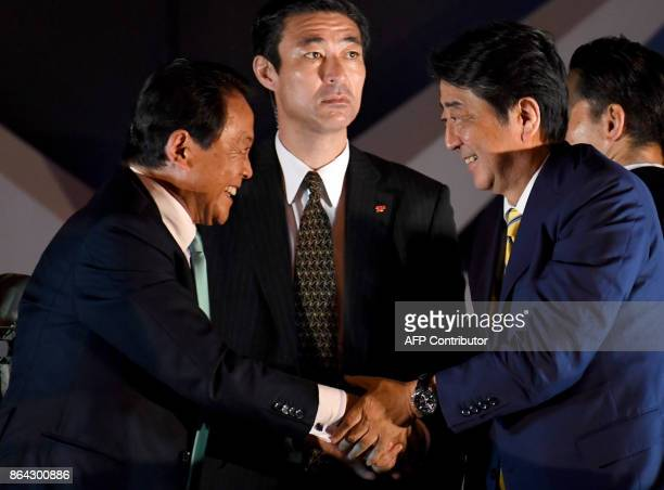 Japan's Prime Minister and ruling Liberal Democratic Party leader Shinzo Abe shakes hands with deputy Prime Minister and Finance Minister Taro Aso...