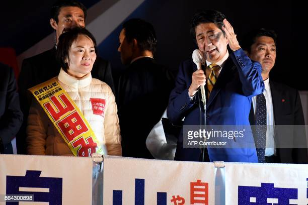 Japan's Prime Minister and ruling Liberal Democratic Party leader Shinzo Abe delivers his speech beside his party candidate Miki Yamada during his...