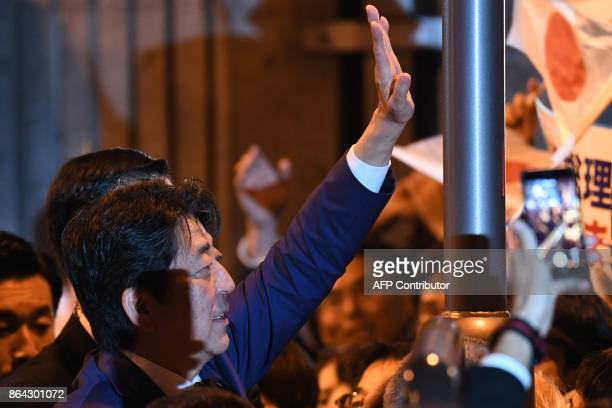 Japan's Prime Minister and ruling Liberal Democratic Party leader Shinzo Abe waves to his supporters during his last stumping tour for the October 22...
