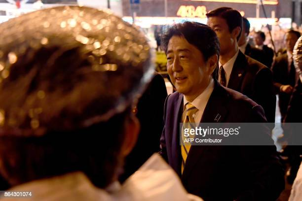 Japan's Prime Minister and ruling Liberal Democratic Party leader Shinzo Abe walks towards his supporters during his last stumping tour for the...