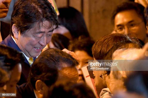 Japan's Prime Minister and ruling Liberal Democratic Party leader Shinzo Abe greets his supporters during his last stumping tour for the October 22...