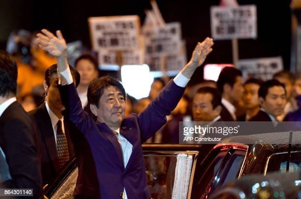Japan's Prime Minister and ruling Liberal Democratic Party leader Shinzo Abe waves to his supporters while leaving his last stumping tour for the...