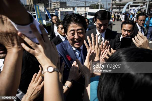 Japan's Prime Minister and ruling Liberal Democratic Party president Shinzo Abe greets supporters during an election campaign in Yaizu Shizuoka...