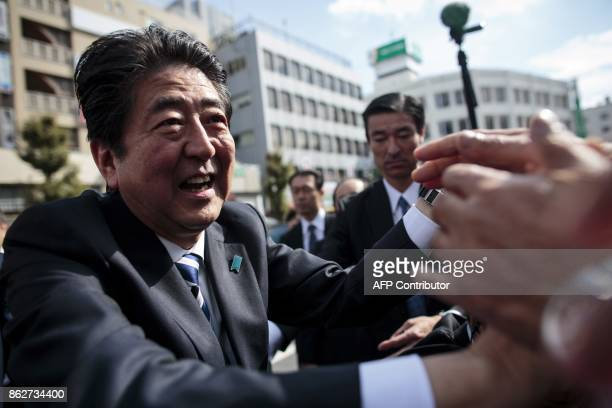 Japan's Prime Minister and ruling Liberal Democratic Party president Shinzo Abe greets his supporters during an election campaign appearance in...