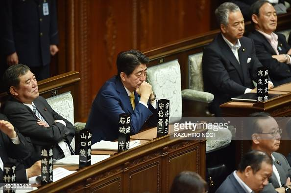 Japan's Prime Minister Shinzo Abe and his cabinet members listen to a speech by a member of an opposition party during a lower house plenary session...
