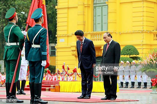 Japan's Prime Minister Shinzo Abe and his Vietnamese counterpart Nguyen Xuan Phuc review an honour guard at the Presidential Palace in Hanoi on...