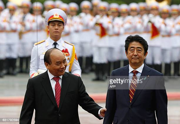 Japan's Prime Minister Shinzo Abe and his Vietnamese counterpart Nguyen Xuan Phuc review the honour guard during a welcoming ceremony at the...